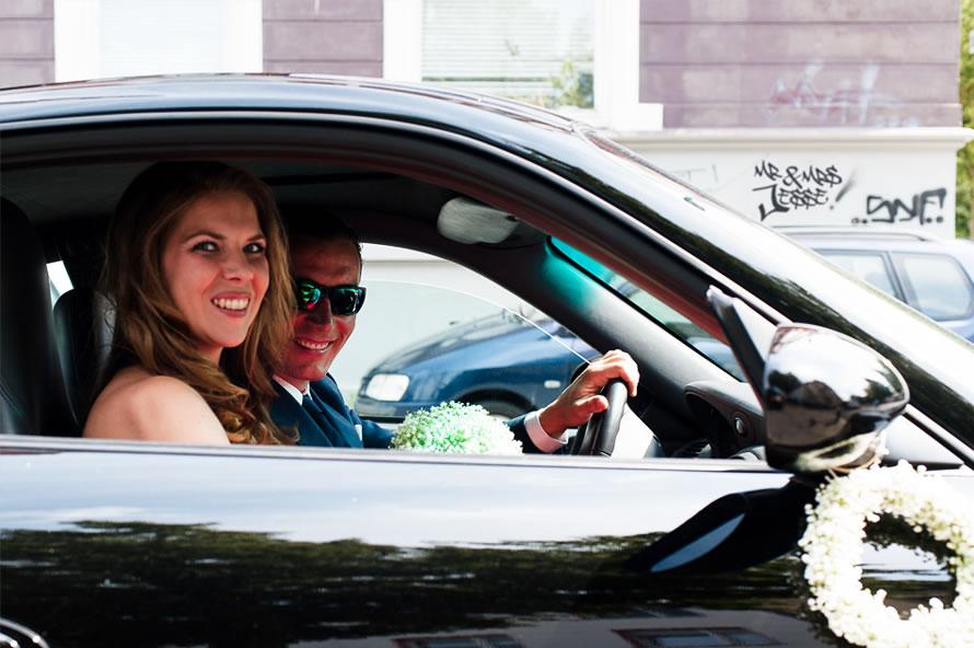 Hochzeitsautodekoration - Brautpaar im Auto