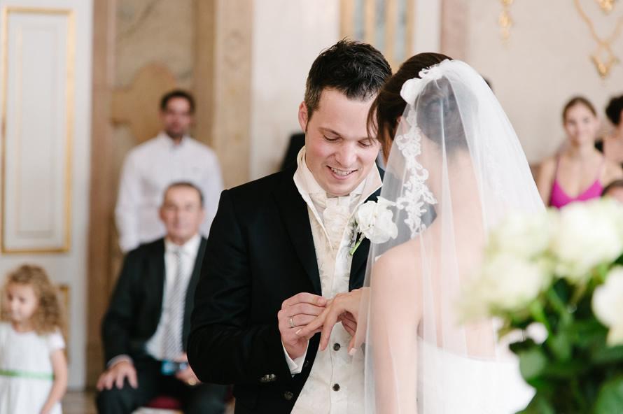 Bräutigam steckt Braut den Ring an