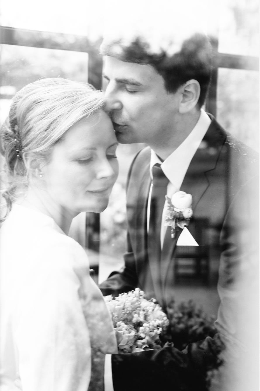 Bräutigam küsst zärtlich seine Braut am hochzeit shooting