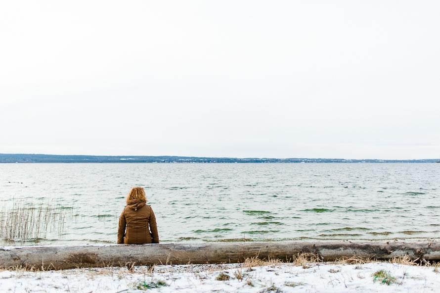 Frau sitzt am See