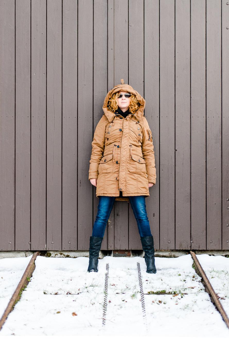 Portrait Frau an einer Holzwand im Wintermantel
