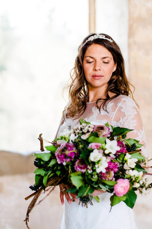 bezaubernde Braut sieht ihren Brautstrauß an