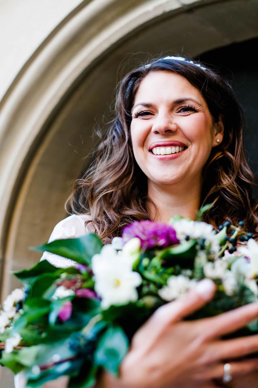 Braut hält freudig Brautstrauß in der Hand