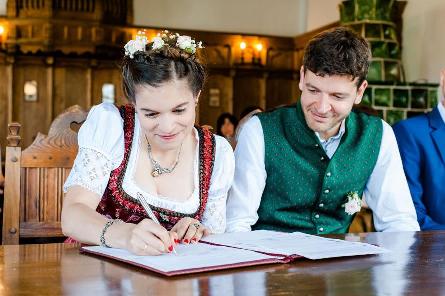 Braut unterschreibt Hochzeitsurkunde