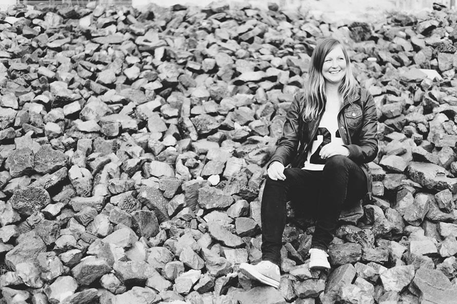 Katja sitzt auf schwarzen Steinen