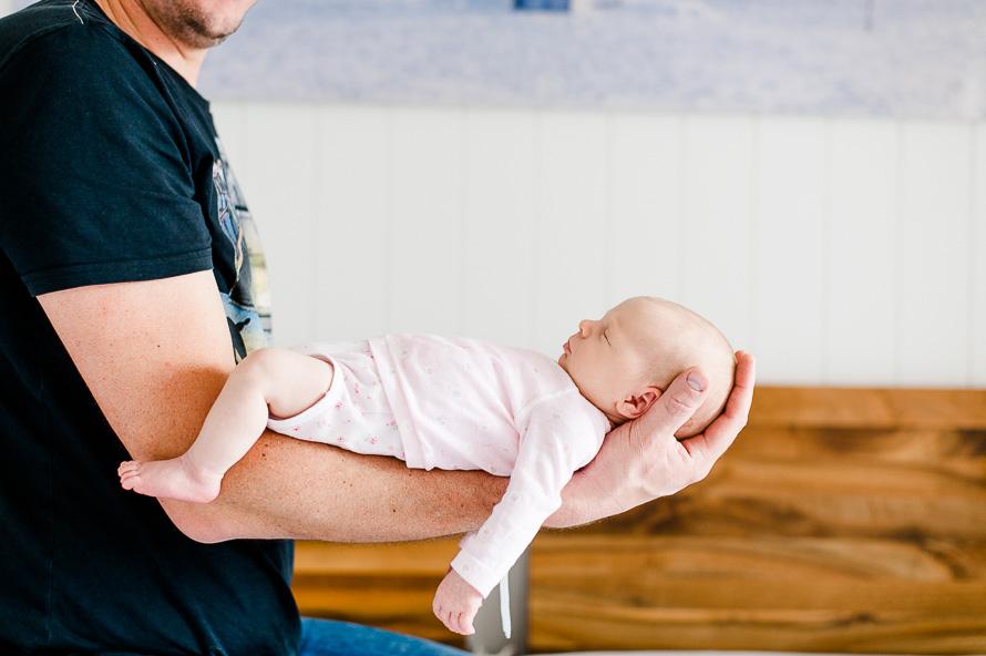 Neugeborenes schläft auf dem Arm von Papa