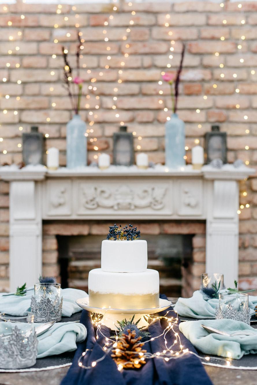 Hochzeitstorte mit schöner Tischdekoratoin vor dem Kamin