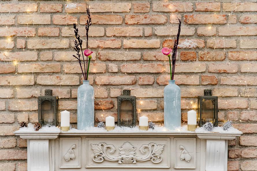 Kamindekoration mit Schnee Tannenzapfen und goldenen Kerzen