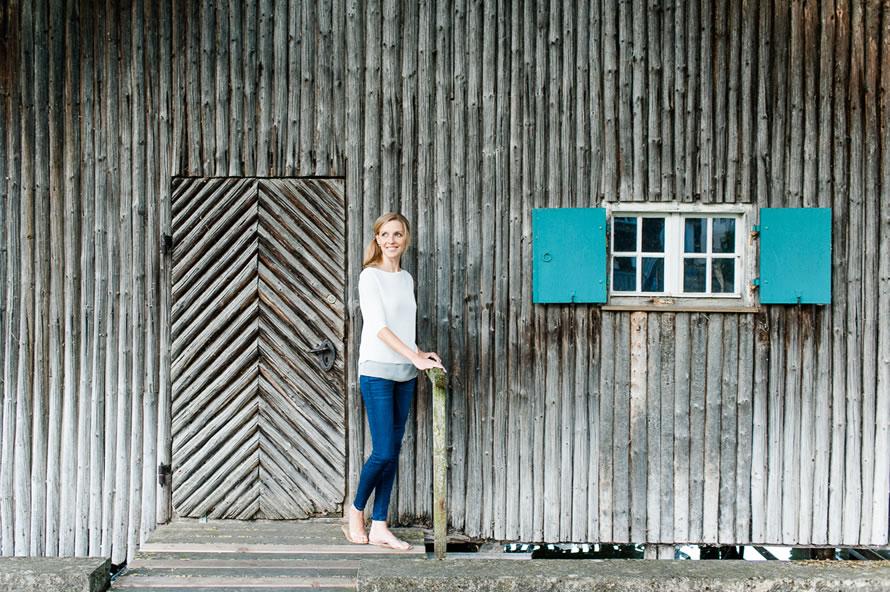 Frau vor einer Holzhütte